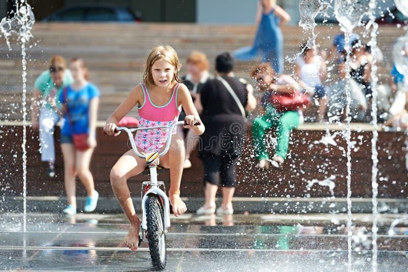 A menina monta sua bicicleta entre fontes imagem de stock