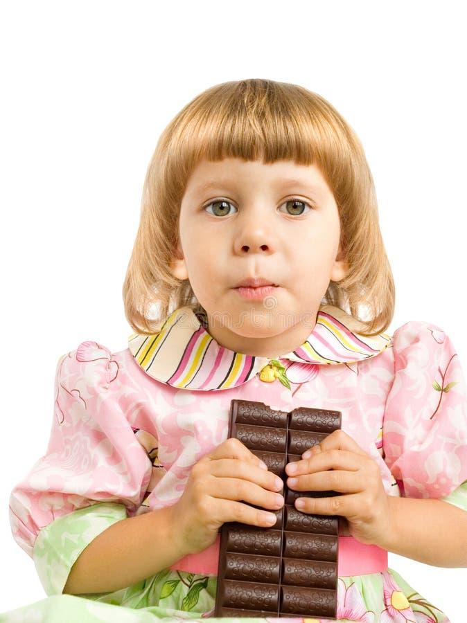 A menina mordeu fora o chocolate fotos de stock royalty free