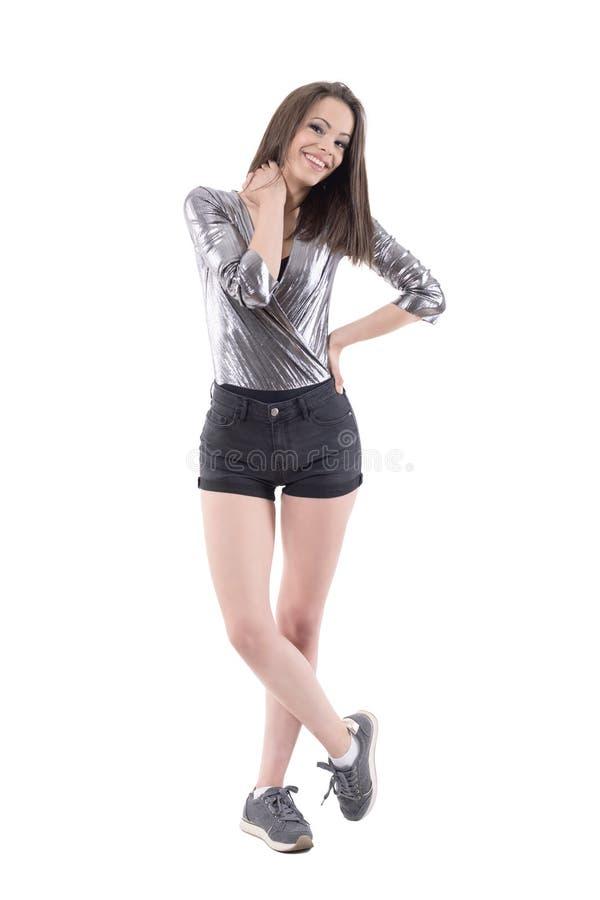 Menina moreno adolescente consideravelmente nova na camisa metálica brilhante e short que sorriem e que olham a câmera imagens de stock