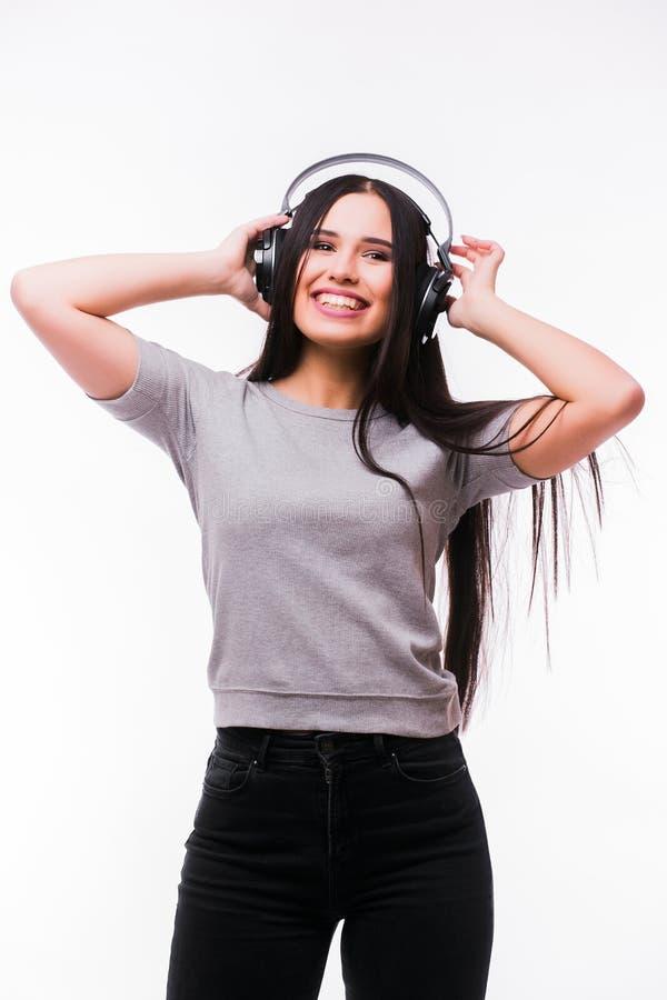 A menina moreno agradável escuta dança a música com fones de ouvido imagem de stock royalty free