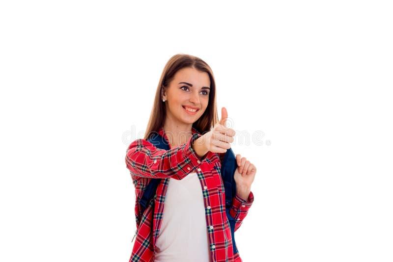 Menina moreno alegre nova do estudante com a trouxa em seus ombros que mostram os polegares isolados acima no fundo branco foto de stock royalty free