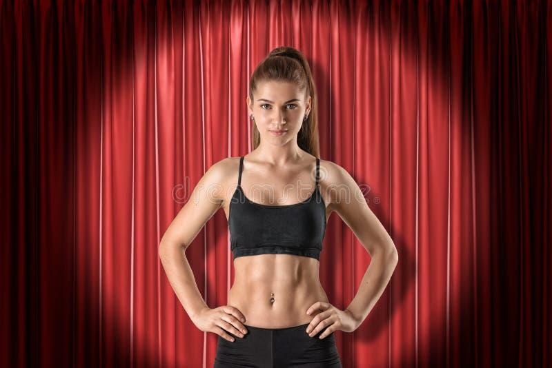 Menina moreno atlética nova na roupa preta do esporte com mãos nos quadris no fundo vermelho das cortinas da fase fotos de stock royalty free