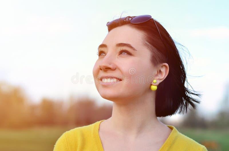 Menina moreno atrativa e bonito em uma camiseta amarela contra a fotografia de stock royalty free