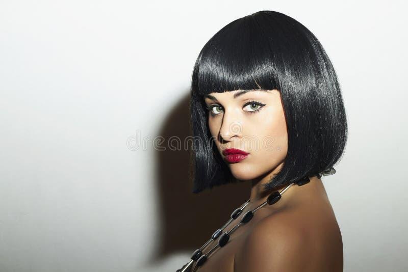 Menina moreno bonita. Cabelo preto saudável. corte de cabelo do prumo. Bordos vermelhos. Mulher da beleza fotos de stock royalty free