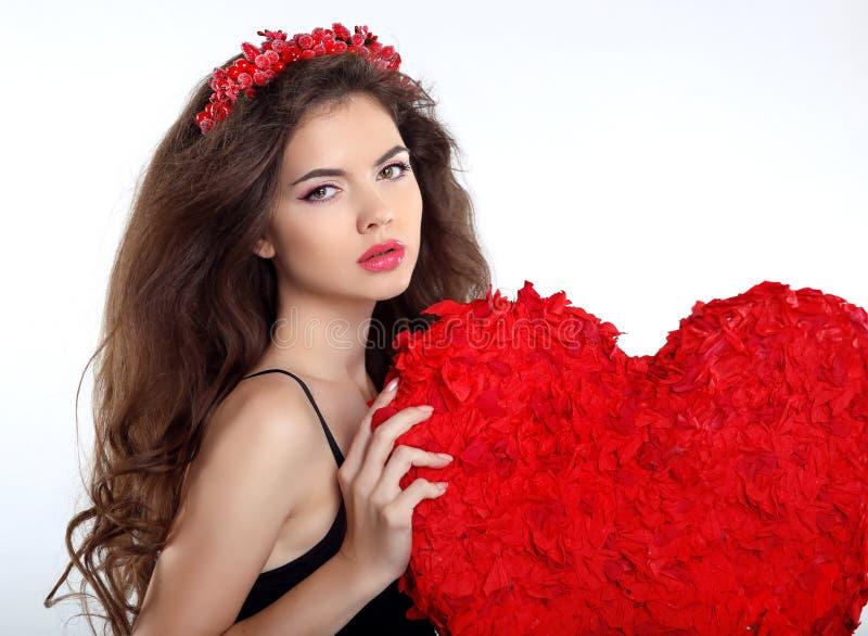 Menina moreno bonita com o presente vermelho do coração para o dia de Valentim fotografia de stock royalty free