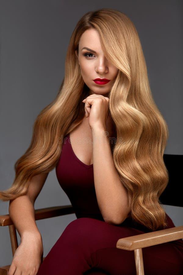 A menina moreno bonita com penteado e compo isolado no fundo branco Mulher bonita com cabelo louro longo ondulado saudável fotografia de stock royalty free