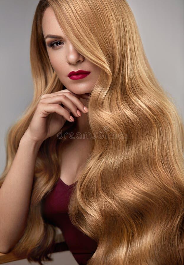 A menina moreno bonita com penteado e compo isolado no fundo branco Mulher bonita com cabelo louro longo ondulado saudável foto de stock royalty free