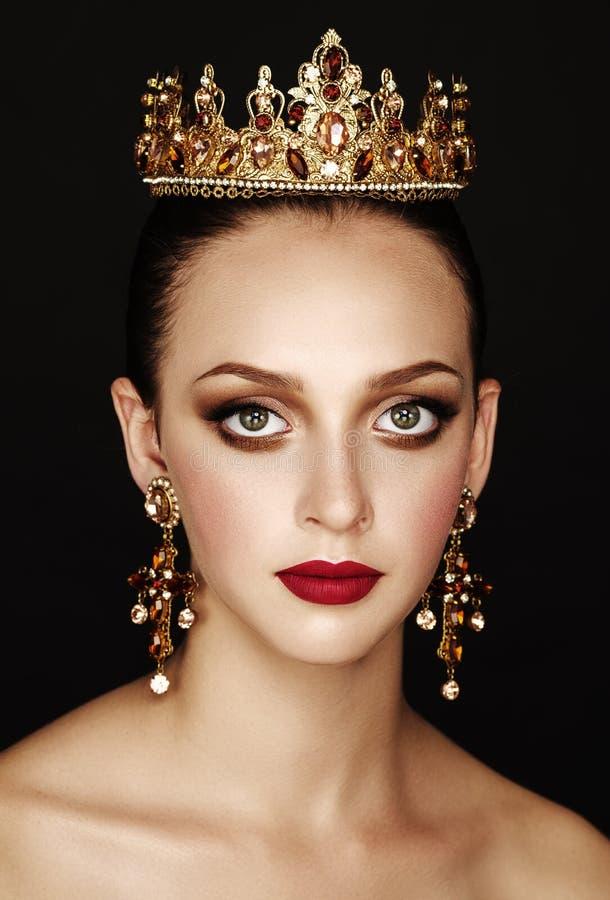 Menina moreno bonita com uma coroa dourada, os brincos e os profes fotografia de stock royalty free