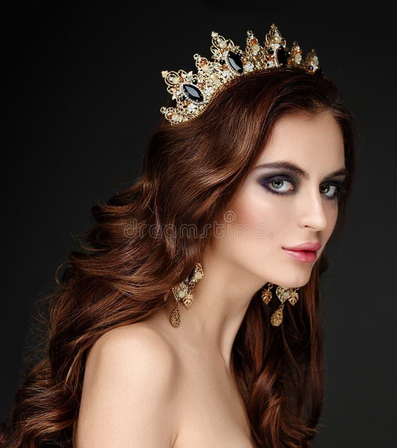 Menina moreno bonita com uma coroa dourada, os brincos e os profes imagem de stock royalty free