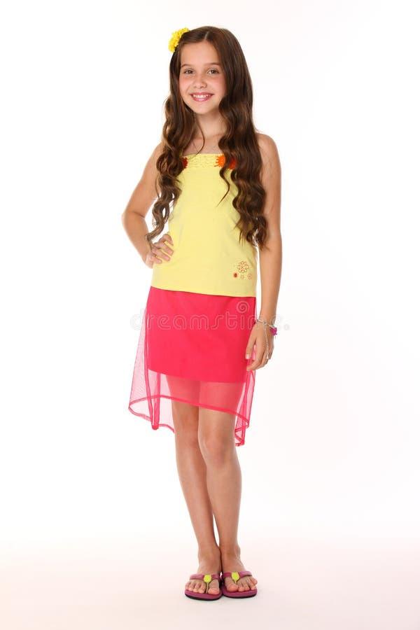 A menina moreno bonita da criança é suportes em uma saia vermelha com pés e sorrisos desencapados imagens de stock