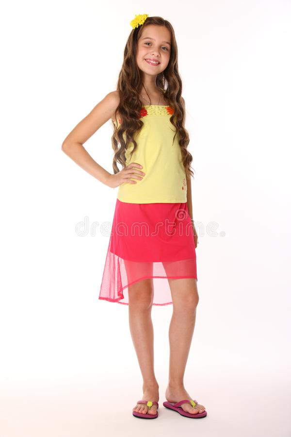 A menina moreno bonita da criança é suportes em uma saia vermelha com pés e sorrisos desencapados foto de stock