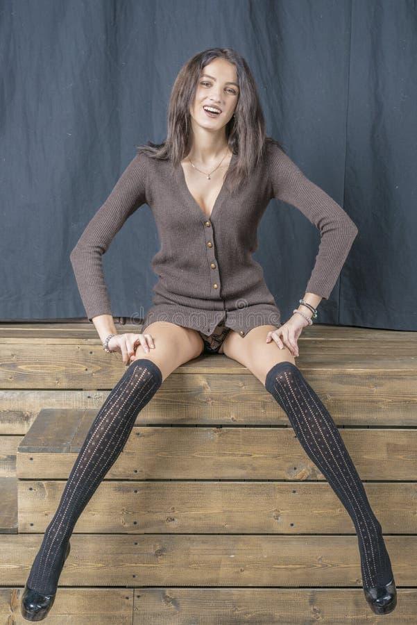 Menina moreno bonita em sorrisos alegres hamming das meias pretas fotografia de stock royalty free