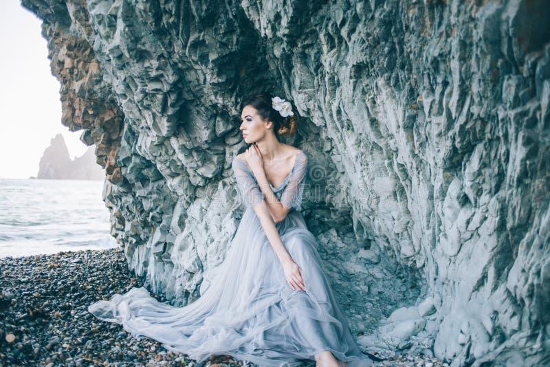 Menina moreno bonita em um vestido cinzento longo com um véu que senta-se pelo mar, fotografia de stock