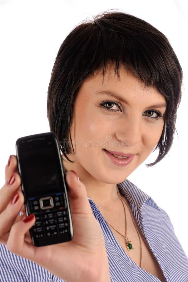 A menina moreno bonita mostra o móbil no telefone imagem de stock
