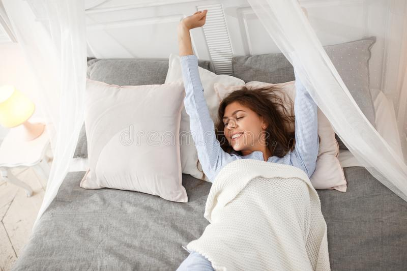 A menina moreno bonita no pijama luz-azul está acordando na cama do dossel sob a cobertura bege na folha cinzenta fotografia de stock
