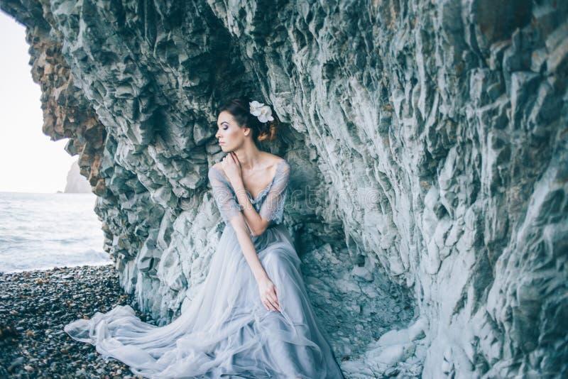 Menina moreno bonita no vestido azul, flor branca no cabelo que senta-se perto do penhasco, o mar, imagens de stock
