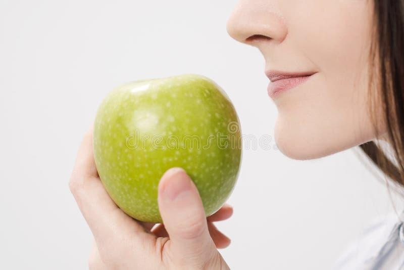 Menina moreno bonita nova em um fundo branco que guarda uma maçã verde fresca foto de stock royalty free