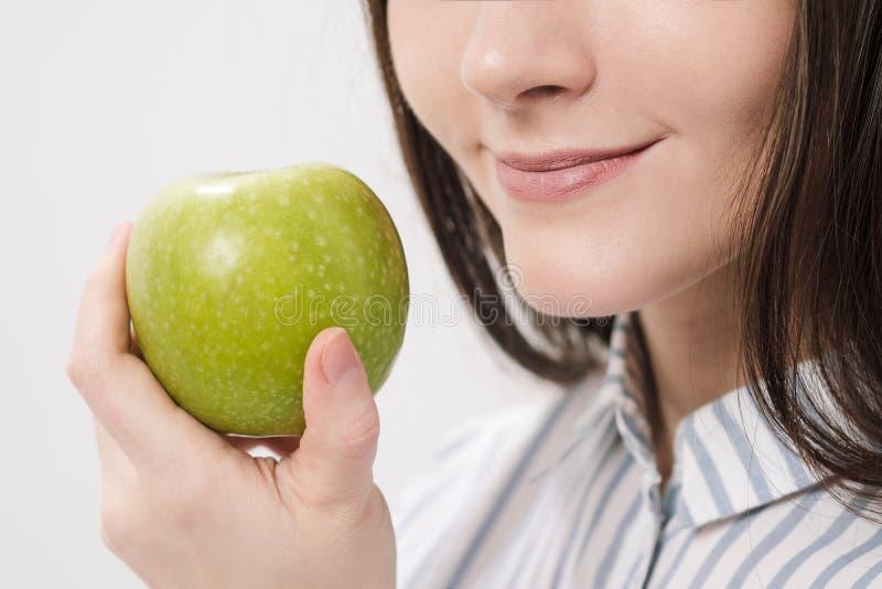 Menina moreno bonita nova em um fundo branco que guarda uma maçã verde fresca fotografia de stock royalty free