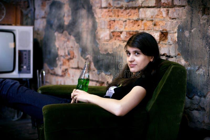 A menina moreno bonita nova está sentando-se em uma cadeira Menina bonita imagem de stock royalty free