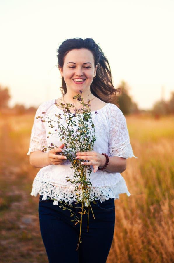 Menina moreno bonita nova feliz com as flores selvagens h do ramalhete fotografia de stock