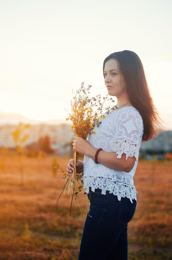 Menina moreno bonita nova feliz com as flores selvagens h do ramalhete foto de stock