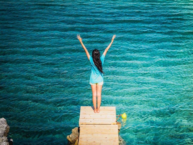 Menina moreno bonita nova no cais do Palm Beach da praia de Preveli, Preveli, Creta Grécia fotografia de stock royalty free