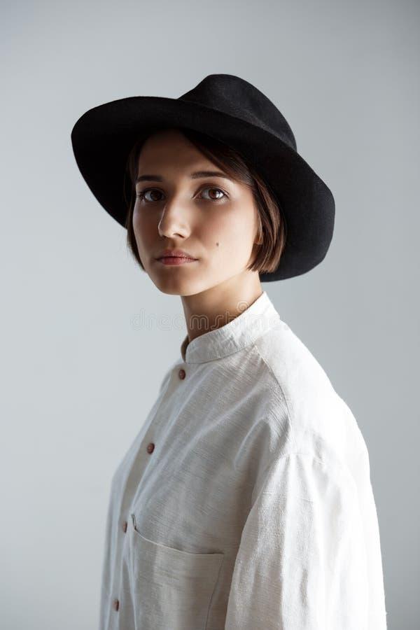Menina moreno bonita nova no chapéu negro sobre o fundo branco fotografia de stock royalty free