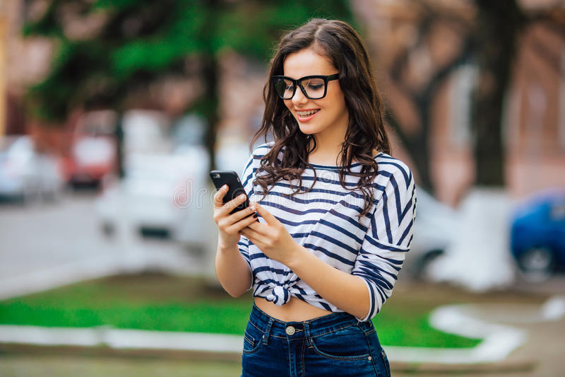 A menina moreno bonita nova nos óculos de sol escuta a música em seu smartphone, imagens de stock