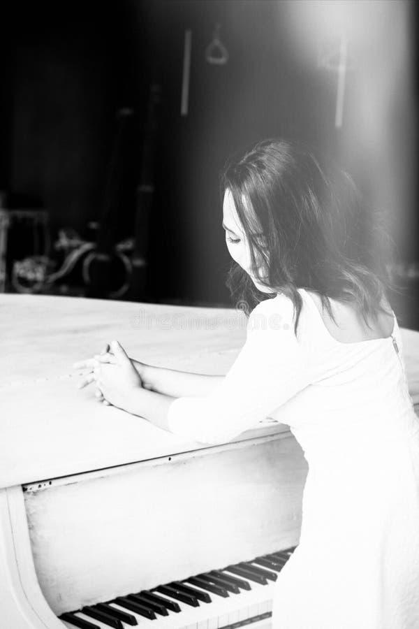 Menina moreno bonita que está em um piano imagens de stock