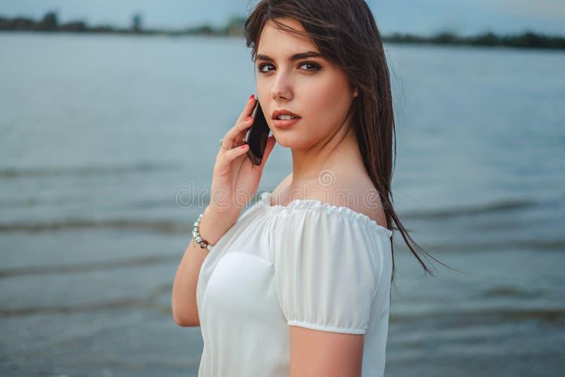 Menina moreno bonita que fala no telefone pelo rio fotos de stock