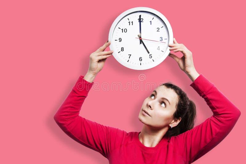 Menina moreno bonita que guarda em volta do pulso de disparo do relógio Cronometre o conceito A menina atrativa nova está olhando imagem de stock royalty free