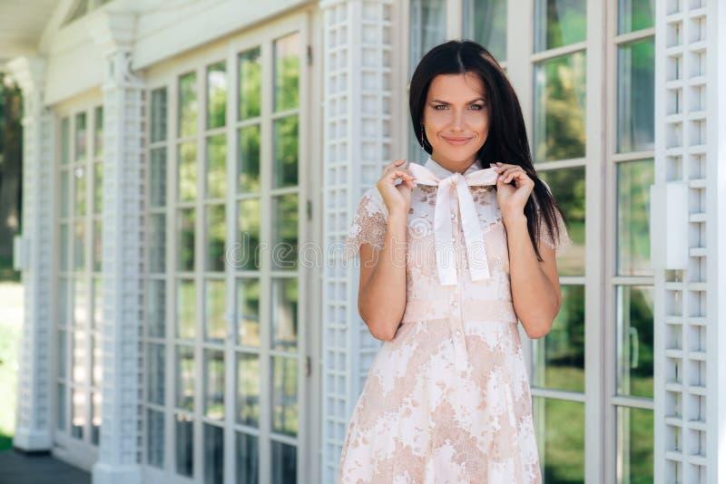 Menina moreno bonita que levanta no vestido bege da cor fora do café perto de uma parede de madeira e de vidro foto de stock