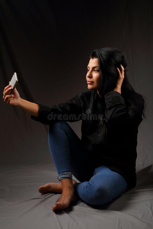 Menina moreno bonita que senta-se no assoalho que toma um selfie imagem de stock royalty free