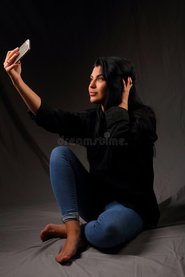 Menina moreno bonita que senta-se no assoalho que toma um selfie imagem de stock