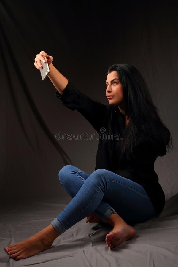 Menina moreno bonita que senta-se no assoalho que toma um selfie fotografia de stock royalty free