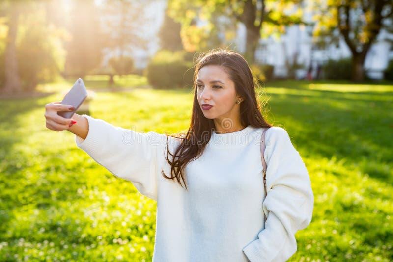 Menina moreno bonita que toma um autorretrato no parque no por do sol imagens de stock royalty free