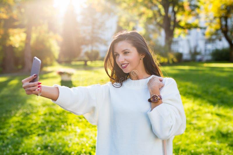 Menina moreno bonita que toma um autorretrato no parque no por do sol imagem de stock royalty free