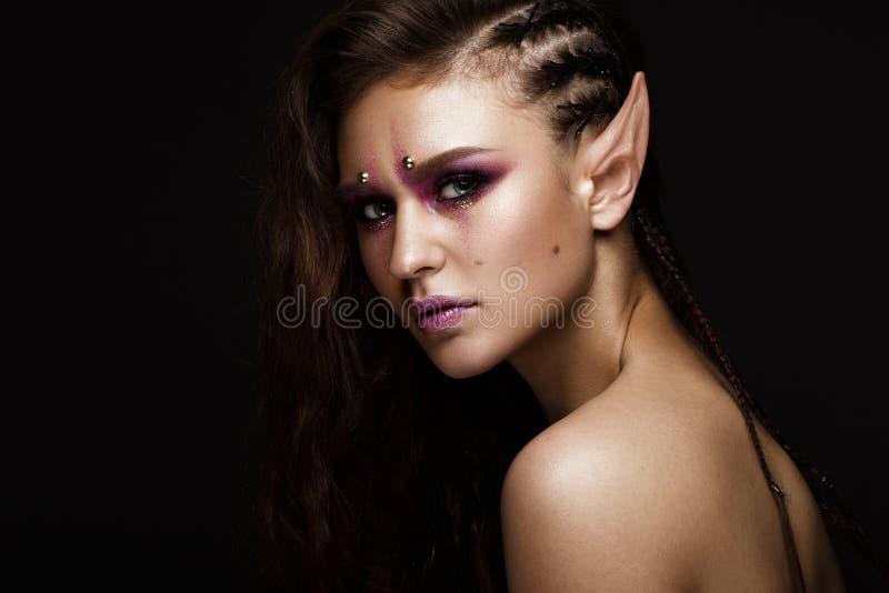 Menina moreno com as tranças criativas de um penteado, a composição da arte e as orelhas do ` s do duende Face da beleza imagens de stock royalty free