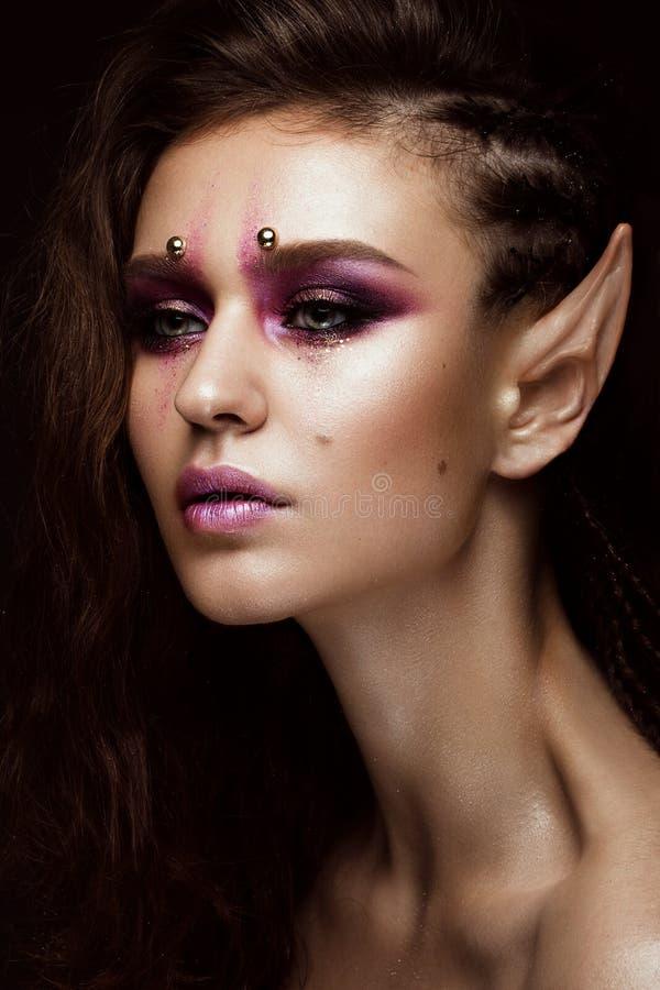 Menina moreno com as tranças criativas de um penteado, a composição da arte e as orelhas do ` s do duende Face da beleza imagem de stock royalty free