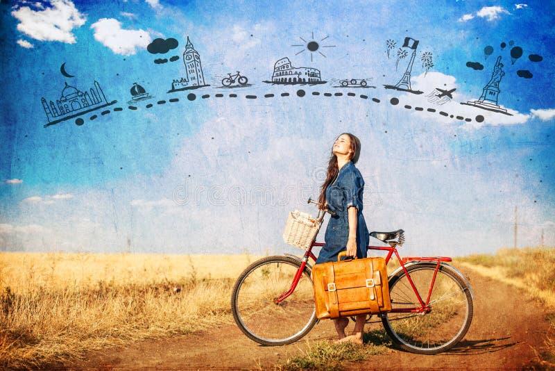 Menina moreno com bycicle e mala de viagem na estrada lateral do país fotos de stock