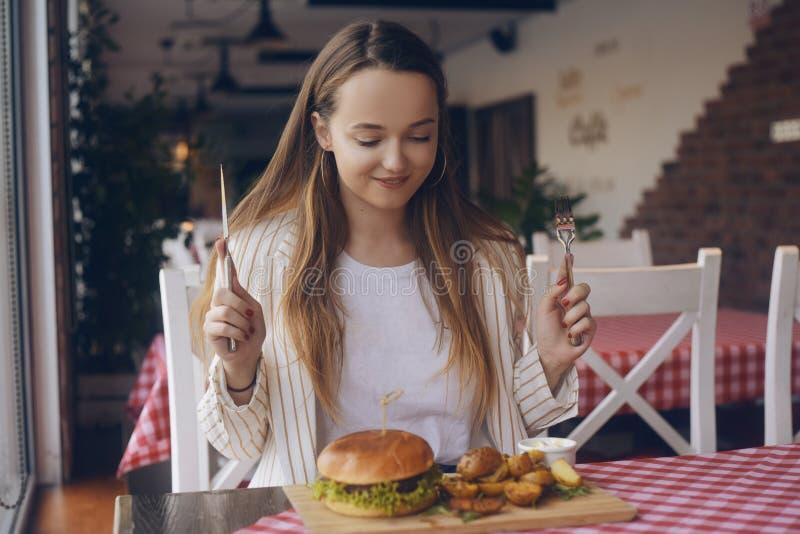 Menina moreno com cabelo longo em batatas apetitosas e em hamburguer comer do restaurante Tentativas hamburguer e fritadas da men imagens de stock