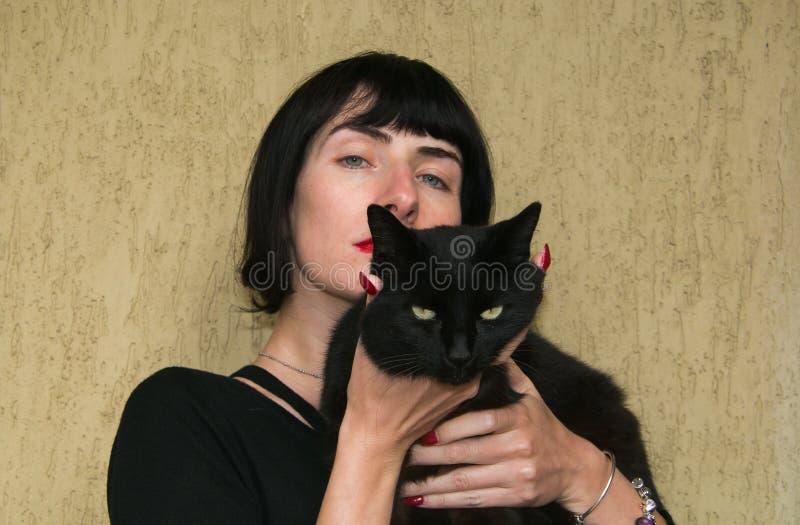 Menina moreno com gato preto fotografia de stock royalty free