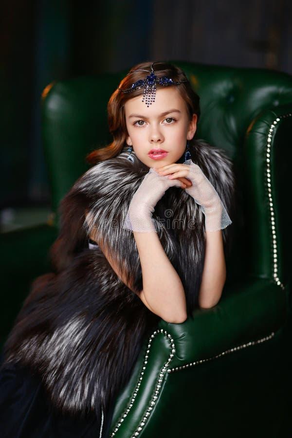 Menina moreno com o acessório do cabelo, as luvas e um casaco de pele fotos de stock royalty free