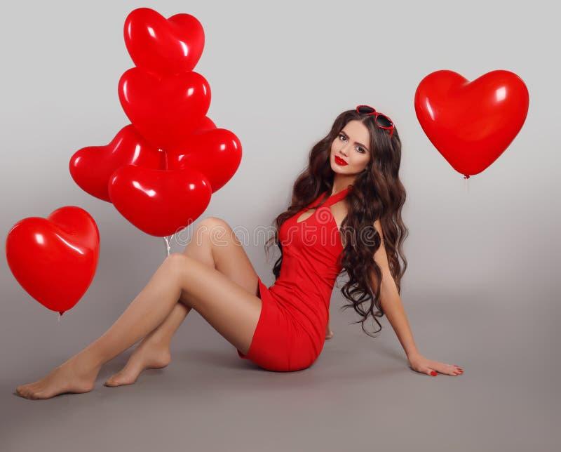A menina moreno consideravelmente bonito no vestido vermelho com forma do coração balloons imagem de stock royalty free
