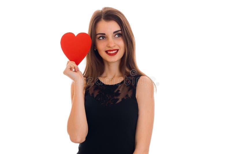 Menina moreno consideravelmente nova que levanta com o coração vermelho isolado no fundo branco Conceito do dia de Valentim de Sa foto de stock royalty free