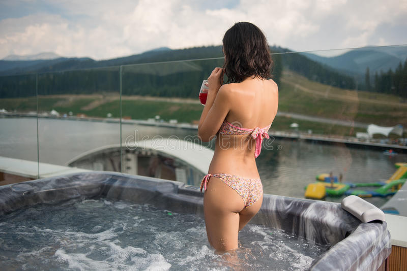 Menina moreno da vista traseira no cocktail bebendo do biquini, estando no Jacuzzi fora em férias fotografia de stock royalty free
