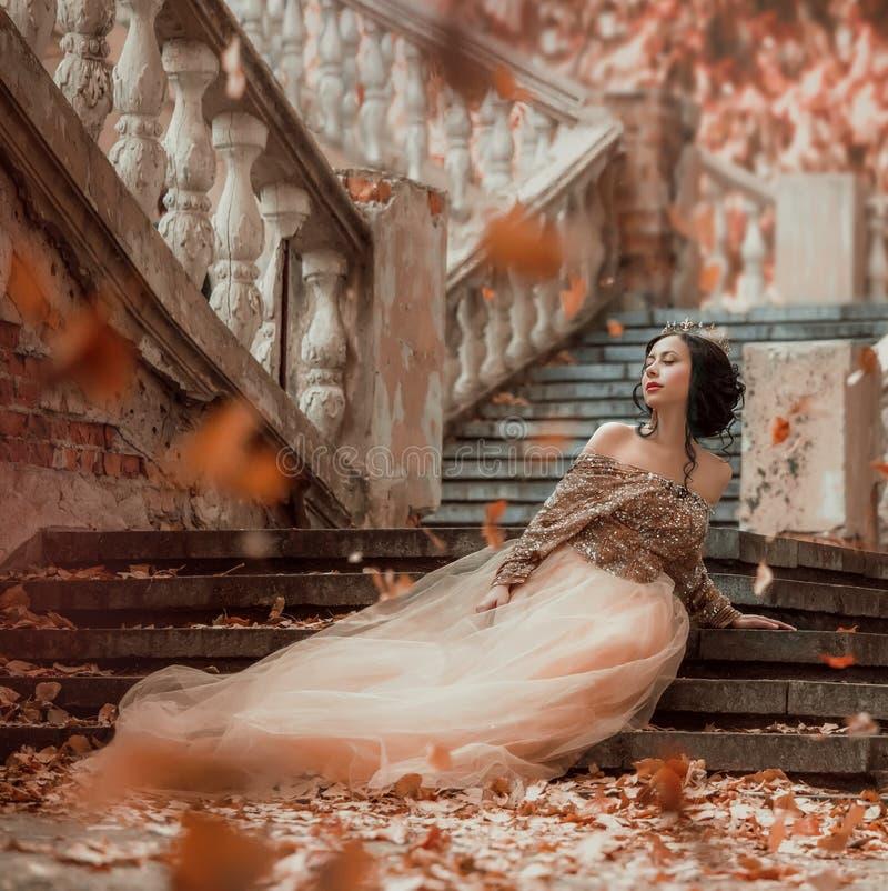 Menina moreno de cabelo escuro encantador atraente que senta-se apenas nas etapas de pedra de um castelo real surpreendente, cons imagens de stock
