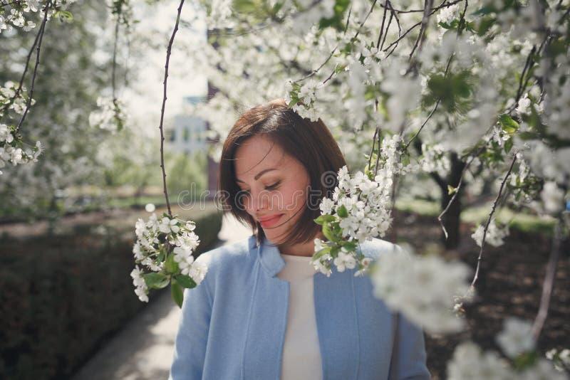 A menina moreno de sorriso bonita com cabelo curto em um revestimento azul está em um jardim florido da mola com uma árvore de ce fotos de stock