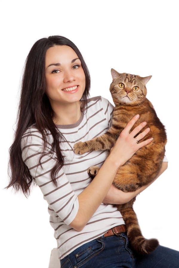 Menina moreno de sorriso bonita e seu gato do gengibre sobre os vagabundos brancos fotos de stock royalty free