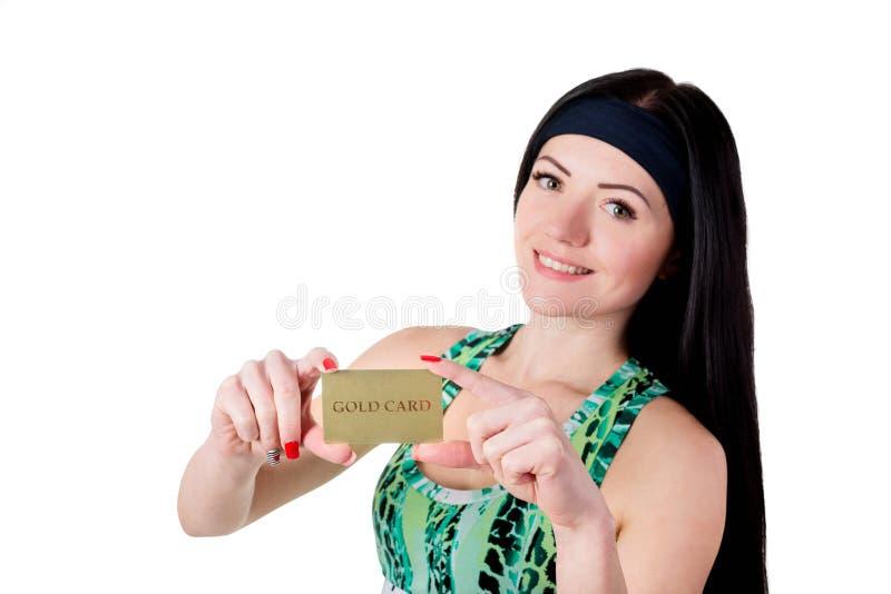 Menina moreno de sorriso com o cabelo longo que mostra o cartão de crédito do ouro foto de stock